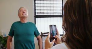 Fisioterapeuta que toma la imagen del hombre mayor con el teléfono móvil 4k almacen de metraje de vídeo