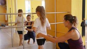 Fisioterapeuta que trabaja con la muchacha en un gimnasio metrajes