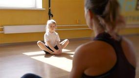 Fisioterapeuta que trabaja con la niña en un gimnasio almacen de video