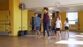 Fisioterapeuta que trabaja con los niños en un gimnasio almacen de video
