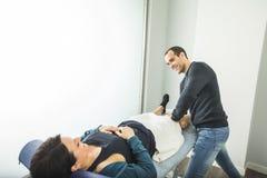 Fisioterapeuta que trata um joelho da jovem mulher Conceito da fisioterapia e da reabilitação fotografia de stock