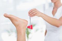Fisioterapeuta que usa el martillo reflejo foto de archivo libre de regalías