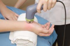 Fisioterapeuta que usa a ponta de prova do ultrassom no paciente 's ha da mulher Fotos de Stock Royalty Free