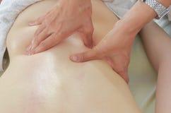 Fisioterapeuta, quiropráctico que da un masaje lumbar a un patie Foto de archivo