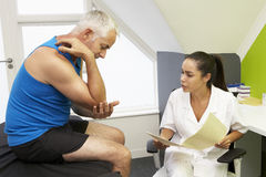 Fisioterapeuta Treating Male Client de los deportes Imagenes de archivo