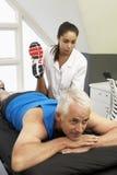 Fisioterapeuta Treating Male Client de los deportes Fotos de archivo libres de regalías