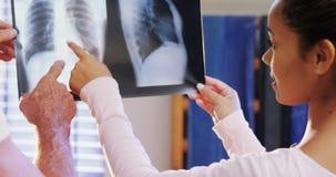 Fisioterapeuta y hombre mayor que discuten sobre la radiografía 4k almacen de video