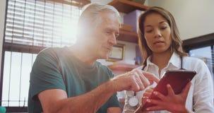 Fisioterapeuta y hombre mayor que usa la tableta digital 4k almacen de metraje de vídeo