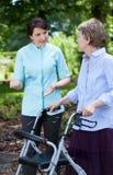 Fisioterapeuta y mujer mayor con el caminante ortopédico Imágenes de archivo libres de regalías