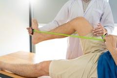 Fisioterapia de consulta da reabilita??o do doutor do fisioterapeuta que d? exercitando o tratamento do p? com o paciente na f?si fotografia de stock