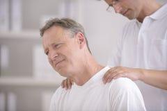 Fisioterapia: Fisioterapeuta que faz massagens o paciente Imagens de Stock
