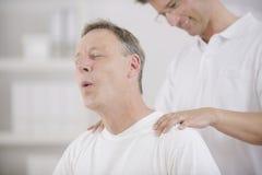 Fisioterapia: Fisioterapeuta que faz massagens o paciente Fotografia de Stock Royalty Free
