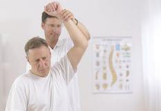 Fisioterapia: Hombre mayor y fisioterapeuta Foto de archivo libre de regalías