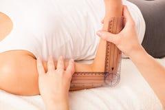 Fisioterapia - terapeuta que excercising com o paciente que usa o gonomete imagens de stock