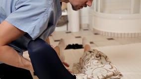 fisioterapia Una donna ottiene un massaggio del piede nel centro di benessere, primo piano Terapia fisica moderna di riabilitazio video d archivio