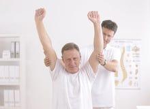 Fisioterapia: Uomo maggiore e fisioterapista Fotografie Stock Libere da Diritti