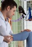 Fisioterapista che allunga la gamba di un paziente Fotografia Stock Libera da Diritti