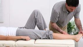 Fisioterapista che allunga la gamba più bassa di una donna archivi video