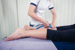 Fisioterapista che applica il nastro di kinesio Immagini Stock