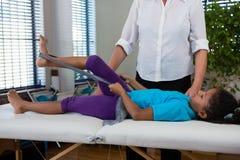 Fisioterapista che assiste il paziente della ragazza nell'esercitarsi d'allungamento dalla banda di resistenza Fotografia Stock