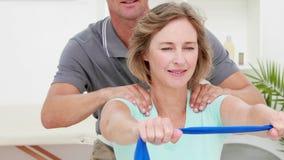 Fisioterapista che controlla paziente che allunga la banda di resistenza