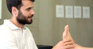 Fisioterapista che dà massaggio del piede ad una donna archivi video
