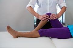 Fisioterapista che dà massaggio della gamba ad un paziente della ragazza Immagini Stock