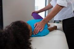 Fisioterapista che dà massaggio della gamba ad un paziente della ragazza Fotografia Stock