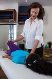 Fisioterapista che dà massaggio della gamba ad un paziente della ragazza Fotografie Stock