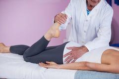 Fisioterapista che dà massaggio della gamba ad una donna Immagini Stock Libere da Diritti