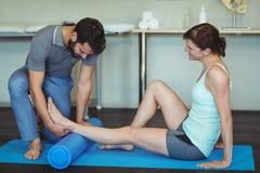 Fisioterapista che dà massaggio della gamba ad una donna sulla stuoia di esercizio Fotografia Stock