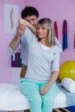 Fisioterapista che dà massaggio della mano al paziente immagini stock libere da diritti
