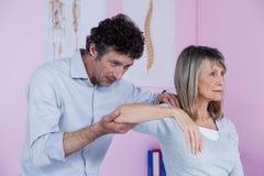 Fisioterapista che dà massaggio della spalla al paziente Fotografie Stock