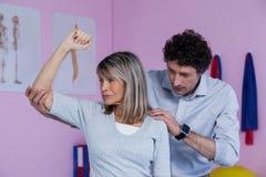 Fisioterapista che dà massaggio della spalla al paziente Fotografia Stock Libera da Diritti