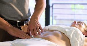 Fisioterapista che dà massaggio dello stomaco ad un paziente femminile archivi video