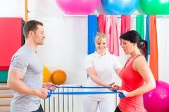 Fisioterapista che dà a pazienti esercizio relativo alla ginnastica Fotografia Stock