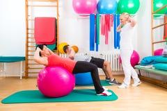 Fisioterapista che dà a pazienti esercizio relativo alla ginnastica Fotografia Stock Libera da Diritti