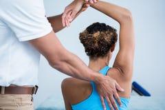 Fisioterapista che dà terapia della spalla ad una donna Fotografia Stock