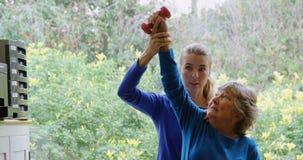 Fisioterapista che dà terapia della spalla con la testa di legno alla donna senior 4k stock footage