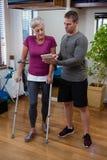 Fisioterapista che discute perizia medica sulla compressa digitale con la donna senior immagini stock