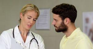 Fisioterapista che discute una perizia medica con il paziente archivi video