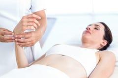 Fisioterapista che esamina il suo polso dei pazienti immagini stock libere da diritti