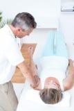 Fisioterapista che fa massaggio del braccio al suo paziente Fotografia Stock