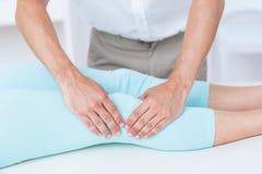 Fisioterapista che fa massaggio della gamba al suo paziente Fotografie Stock Libere da Diritti