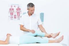 Fisioterapista che fa massaggio della gamba al suo paziente Immagini Stock