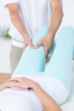 Fisioterapista che fa massaggio della gamba al suo paziente Immagine Stock