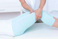 Fisioterapista che fa massaggio della gamba al suo paziente Immagini Stock Libere da Diritti