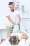 Fisioterapista che fa massaggio della gamba al suo paziente Immagine Stock Libera da Diritti