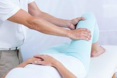 Fisioterapista che fa massaggio della gamba al suo paziente Fotografia Stock