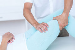 Fisioterapista che fa massaggio della gamba al suo paziente Fotografia Stock Libera da Diritti